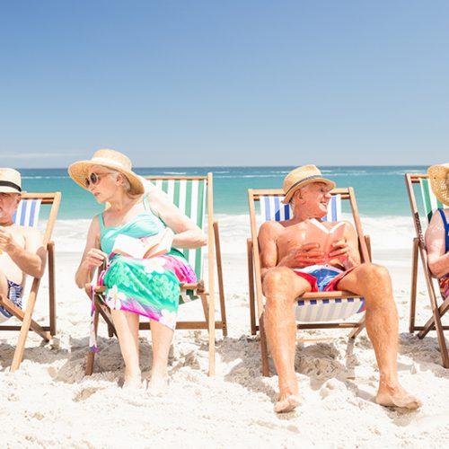 Voksne mennesker på solseng langs stranden